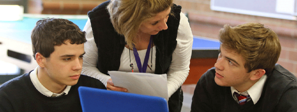 Female adult talking to two male students