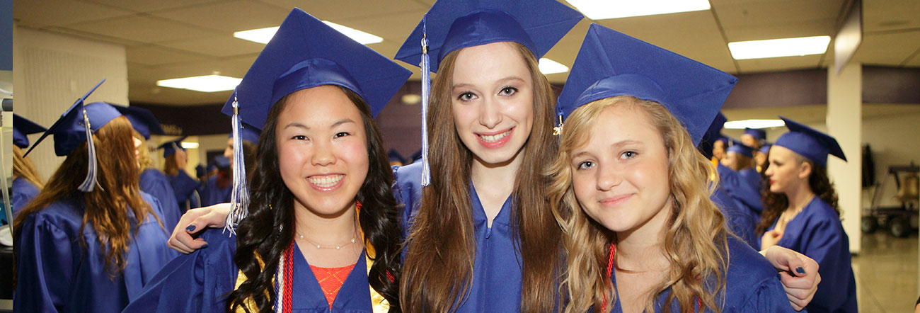 Three female students in graduation cap and gown